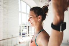 做健身的被晒黑的健康妇女画象在晴朗的健身房行使 免版税图库摄影