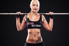 做健身的运动的美丽的妇女行使在黑背景停留适合 健身锻炼刺激 免版税库存照片