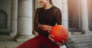 做健身训练的一个女运动员的播种的射击使用篮球 做锻炼的微笑的健身妇女拿着球 免版税库存照片