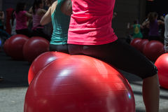 做健身活动的女孩特写镜头坐大红色球 库存图片