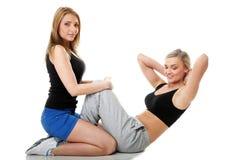 做健身锻炼的两名妇女  免版税库存照片