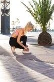 做健身锻炼的女运动员外面在棕榈公园 库存照片