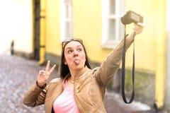做傻的面孔和显示舌头的少妇对照相机 免版税图库摄影