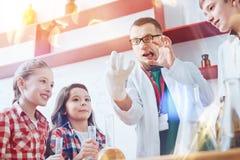 做傻的面孔的滑稽的家庭教师在与孩子的科学实验期间 免版税库存图片