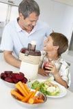 做儿子蔬菜的父亲新鲜的汁液 免版税图库摄影