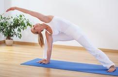 做先进的瑜伽锻炼的妇女 免版税库存图片