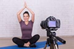 做关于体育和瑜伽的亭亭玉立的妇女博客作者录影 库存图片