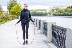 做准备与跳绳的运动的妇女户外 免版税库存图片