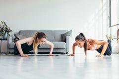 做准备两名健身的妇女做俯卧撑行使在家解决 免版税库存图片