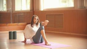 做准备在地板上和做在她的腿的年轻女人体操运动员锻炼 股票录像