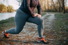 做准备在跑前的超重妇女在公园 库存图片
