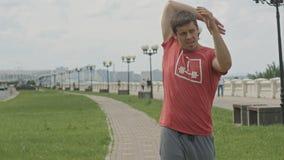 做准备在跑步前的英俊的运动员户外 免版税库存照片