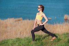 做准备在跑步前 体育的做的衣物和的太阳镜可爱的少妇舒展锻炼和看concent 库存图片