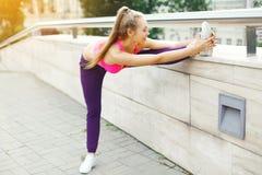 做准备的健身少妇舒展锻炼在奔跑、女运动员准备好对锻炼在城市,体育和健康前 免版税库存图片