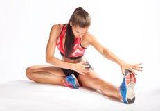 做准备美丽的女运动员,舒展她的在白色b的腿 免版税图库摄影