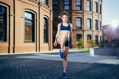 做准备锻炼的少妇在跑前舒展她的在城市街道上的腿 免版税图库摄影