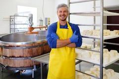做凝乳酪的英俊的乳酪商在他的工厂 免版税库存照片