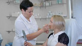 做凹道更正的美容师在妇女面孔排行 库存照片