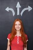 做出决定的快乐的妇女站立在黑板背景 免版税库存图片