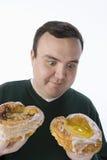 做出在两个油炸圈饼之间的人一个选择 免版税库存图片
