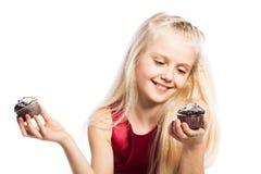 做出在两个蛋糕之间的女孩一个选择 免版税库存图片