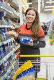 做出在两盒的妇女一个选择面团之间在大型超级市场商店,站立与杂货推车 免版税库存图片