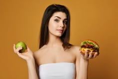 做出在健康食品苹果和便当汉堡之间的年轻女人决定 健身、饮食和食物概念-怀疑妇女 免版税库存照片