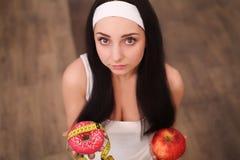 做出在苹果和多福饼之间的美丽的少妇选择在木背景 免版税库存图片