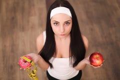 做出在苹果和多福饼之间的美丽的少妇选择在木背景 库存图片