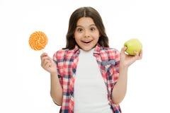 做出正确的选择 能加糖甜口味使我们愉快 女孩拿着甜棒棒糖和苹果 学校午餐选择 免版税图库摄影