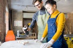 做创造性的木制品的两位艺术家 免版税库存图片