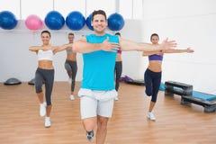 做力量健身的微笑的人民在健身演播室行使 免版税库存图片