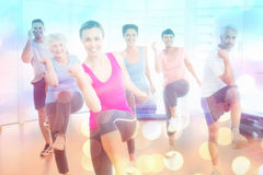 做力量健身的微笑的人民的综合图象行使在瑜伽类 免版税图库摄影