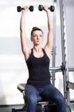 做力量健身锻炼的美丽的运动的妇女在体育健身房 库存照片