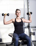 做力量健身锻炼的美丽的运动的妇女在体育健身房 库存图片