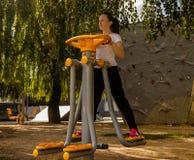 做加强的女孩腿锻炼,室外 图库摄影