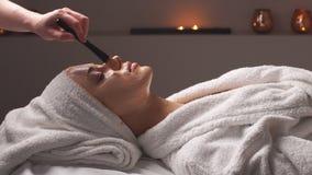 做化妆面部面具的女性美容师对女性客户在整容术中心 股票录像