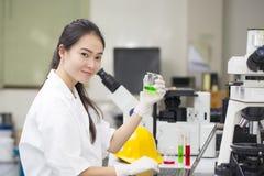 做化工测试的科学家在实验室 免版税库存图片