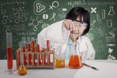 做化工测试的逗人喜爱的女学生 免版税库存图片