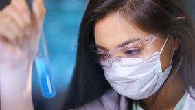 做化工考试的防护玻璃面具的亚裔女性研究员毒性物质 股票录像