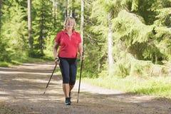 做北欧步行锻炼的活跃资深妇女 免版税库存照片