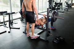 做卧推的英俊的年轻肌肉人和得到帮助 免版税库存照片
