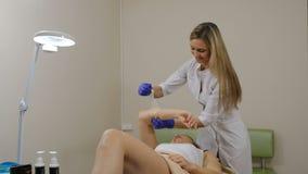 做去壳的美容院的少妇 epilation 美容师与手一起使用 射击在4k 影视素材