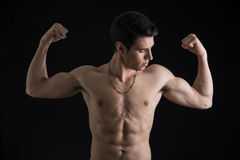 做双重二头肌的赤裸上身的肌肉年轻人 图库摄影