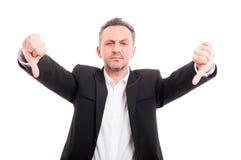 做双重拇指的商人下来打手势 免版税库存图片