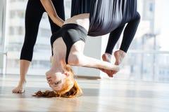 做反地心引力的瑜伽的姿势与个人教练员的俏丽的妇女 免版税库存图片