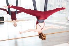 做反地心引力的瑜伽的姿势妇女使用吊床 免版税库存图片