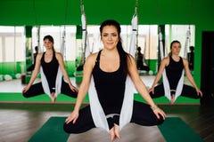 做反地心引力的瑜伽的少妇行使与一群人 航空飞行健身教练员锻炼 白色吊床 免版税库存照片
