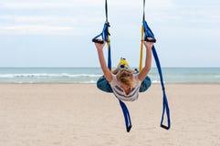 做反地心引力的瑜伽的少妇 飞行瑜伽行使与在海背景的黄色,蓝色吊床 健康寿命 免版税库存照片