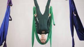 做反地心引力的飞行瑜伽的年轻白种人妇女在吊床行使在演播室户内 空中航空飞行健身 影视素材